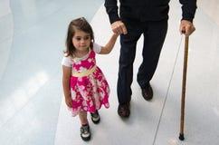 Kleines Mädchen, das ihrem Urgroßvater hilft und stützt Lizenzfreie Stockfotografie