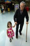 Kleines Mädchen, das ihrem Urgroßvater hilft und stützt Stockfotografie