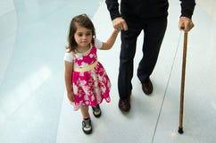 Kleines Mädchen, das ihrem Urgroßvater hilft und stützt Stockfotos