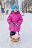 Kleines Mädchen, das in ihren Händen einen Korb mit Ostereiern und einem Hahn, Tag des Winters auf der Straße im Park hält Lizenzfreie Stockbilder