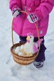 Kleines Mädchen, das in ihren Händen einen Korb mit Ostereiern und einem Hahn, Tag des Winters auf der Straße im Park hält Stockfoto