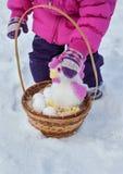 Kleines Mädchen, das in ihren Händen einen Korb mit Ostereiern und einem Hahn, Tag des Winters auf der Straße im Park hält Lizenzfreies Stockfoto