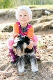 Kleines Mädchen, das ihren Hund umarmt Stockfotografie