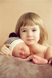 Kleines Mädchen, das ihren neugeborenen schlafenden Bruder umarmt Für die Liebe O stockbilder