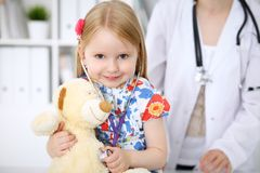 Kleines Mädchen, das ihren Teddybären durch Stethoskop überprüft Gesundheitswesen, Kinderpatientenvertrauenskonzept Stockfoto