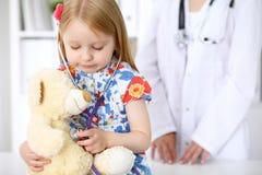 Kleines Mädchen, das ihren Teddybären durch Stethoskop überprüft Gesundheitswesen, Kinderpatientenvertrauenskonzept Lizenzfreie Stockbilder