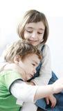 Kleines Mädchen, das ihren Umkippenbruder umarmt Stockbilder