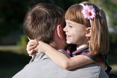 Kleines Mädchen, das ihren Vater umfassend umarmt Stockbilder