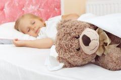 Kleines Mädchen, das im Bett mit ihrem Teddybären schläft lizenzfreie stockfotografie