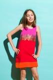 Kleines Mädchen, das im bunten Kleid aufwirft Stockfotografie