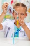 Kleines Mädchen, das im Chemieunterricht experimentiert Stockfoto