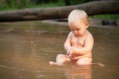 Kleines Mädchen, das im Fluss sitzt Lizenzfreies Stockfoto