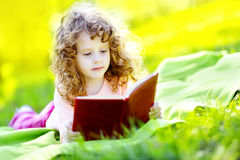 Kleines Mädchen, das im Frühjahr einen Park des Buches liest Stockfotos