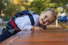 Kleines Mädchen auf einer Bank Lizenzfreies Stockfoto