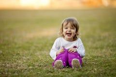 Kleines Mädchen, das im Gras, lachend spielt Lizenzfreies Stockbild