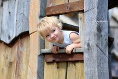Kleines Mädchen, das im Holzhaus im Park spielt Lizenzfreies Stockfoto