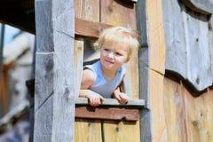 Kleines Mädchen, das im Holzhaus im Park spielt Lizenzfreie Stockfotos