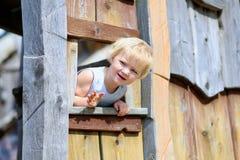 Kleines Mädchen, das im Holzhaus im Park spielt Stockbilder