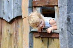 Kleines Mädchen, das im Holzhaus im Park spielt Lizenzfreie Stockbilder