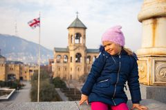 Kleines Mädchen, das im Kathedralenhof der Heiligen Dreifaltigkeit mit georgischer Flagge im Hintergrund seeting ist lizenzfreies stockfoto