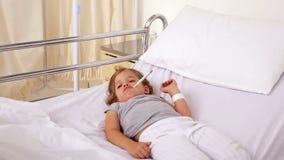 Kleines Mädchen, das im Krankenhausbett mit einem Thermometer liegt stock footage