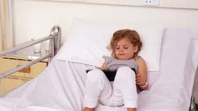 Kleines Mädchen, das im Krankenhausbett unter Verwendung einer Tablette liegt stock video