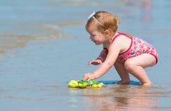 Kleines Mädchen, das im Meer am Strand spielt Stockfotografie