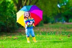 Kleines Mädchen, das im Regen hält bunten Regenschirm spielt Stockfoto