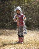 Kleines Mädchen, das im Regen spielt Stockfotos