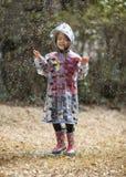 Kleines Mädchen, das im Regen spielt Lizenzfreie Stockfotografie
