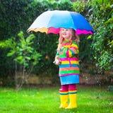 Kleines Mädchen, das im Regen unter buntem Regenschirm spielt Lizenzfreies Stockbild