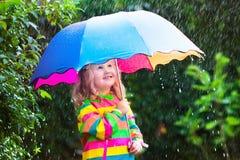 Kleines Mädchen, das im Regen unter Regenschirm spielt Stockbilder