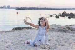 Kleines Mädchen, das im Sand an der Dämmerung spielt lizenzfreie stockbilder