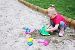 Kleines Mädchen, das im Sand spielt Lizenzfreies Stockbild