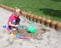 Kleines Mädchen, das im Sand spielt Lizenzfreie Stockfotografie