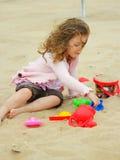 Kleines Mädchen, das im Sand spielt Stockbild