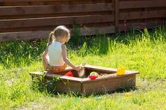 Kleines Mädchen, das im Sandkasten abspielen sitzt Lizenzfreie Stockfotos