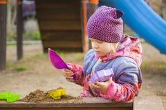 Kleines Mädchen, das im Sandkasten auf dem Spielplatz spielt Stockfotos