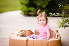 Kleines Mädchen, das im Sandkasten an einem sonnigen Sommertag spielt Stockbild