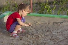 Kleines Mädchen, das im Sandkasten an einem sonnigen Sommertag spielt Lizenzfreie Stockfotografie