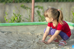 Kleines Mädchen, das im Sandkasten an einem sonnigen Sommertag spielt Lizenzfreie Stockbilder