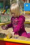 Kleines Mädchen, das im Sandkasten spielt Lizenzfreie Stockfotos