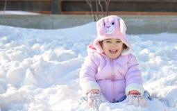 Kleines Mädchen, das im Schnee spielt Lizenzfreie Stockfotos