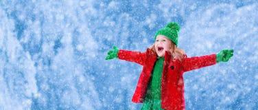 Kleines Mädchen, das im schneebedeckten Park spielt Stockbilder