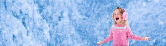 Kleines Mädchen, das im schneebedeckten Park spielt Lizenzfreie Stockfotos