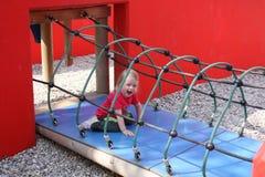 Kleines Mädchen, das im Spielplatz spielt Lizenzfreie Stockfotos