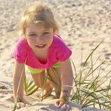 Kleines Mädchen, das im Strandsand spielt Lizenzfreie Stockfotos