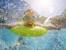 Kleines Mädchen, das im Swimmingpool spielt lizenzfreie stockbilder