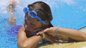 Kleines Mädchen, das im Swimmingpool spielt stock video