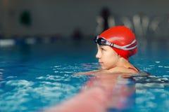 Kleines Mädchen, das im Swimmingpool stillsteht stockfotos